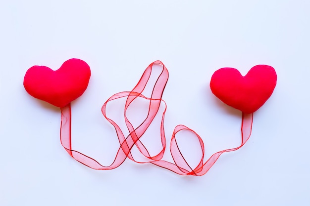 Valentine's hearts with red ribbon on white paper background.