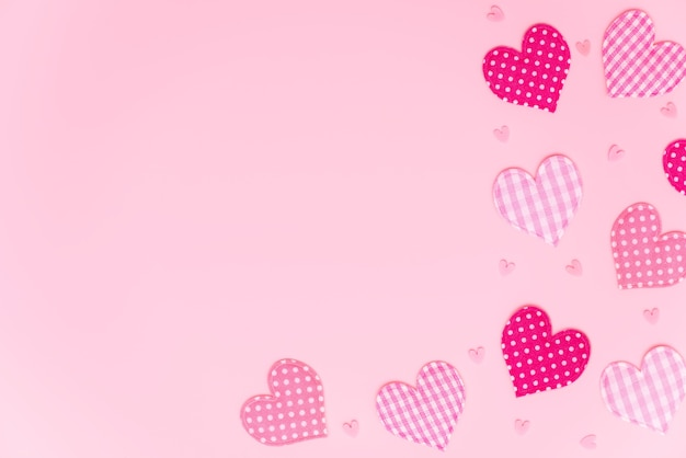 Valentine's or mother's day background. fabric hearts with different patterns on pastel pink with