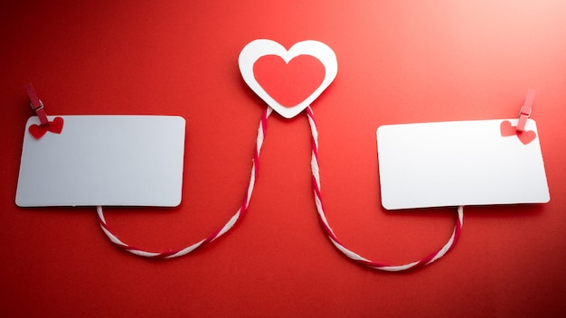 Valentine's paper hearts with a blank business card and clothespin on a red background