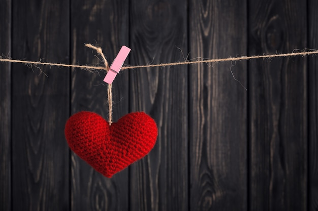 Valentine's red heart on rope on wooden background