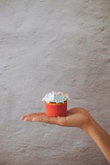 明るい背景の手にバレンタインの甘い愛のカップケーキ