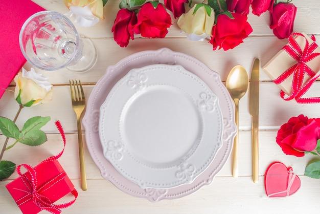 バレンタインテーブルの設定。プレート、銀器、シャンパンワイングラス、ギフトボックス、バラの花束を備えたテーブルディナーの場所上面図のコピースペース