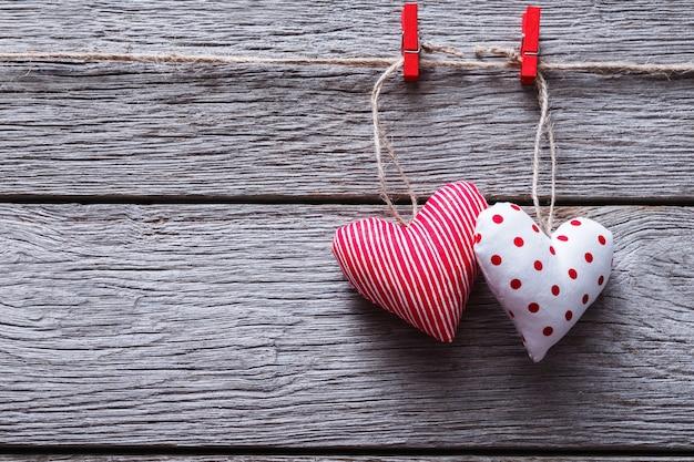 Валентинка с сердечками из сшитых вручную подушек на красных прищепках на синих деревянных досках