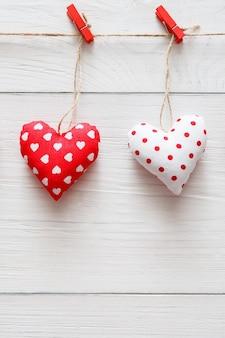 Валентинка с сшитой подушкой поделки ручной работы пара сердечек на красных прищепках на деревенских белых деревянных досках
