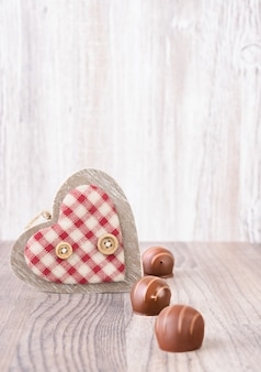 Valentine with wooden heart and chocolate pralines