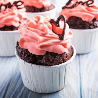 バレンタインと母の日、美しいチョコレートカップケーキ、ピンクのクリームと青い木の表面にハートの結婚式のグリーティングカード