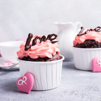 バレンタインと母の日、コピースペースのある灰色の石の表面に美しいチョコレートカップケーキ、ピンクのクリームとハートの結婚式のグリーティングカード