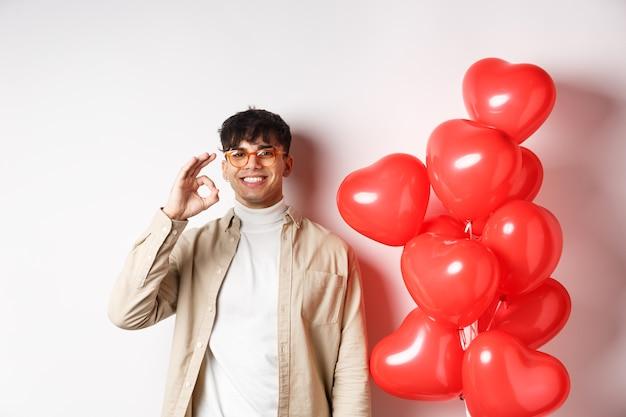 バレンタインとロマンスのコンセプト。幸せな若い男は笑顔で、赤いハートのジェスチャーの近くにokのサインを示し、恋人の日に良いオファーをお勧めします。