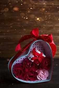 Валентина фон с красными сердцами и розы в подарочной коробке на темном деревянном фоне