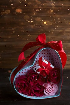 Valentines background with red hearts and rose in gift box on dark wooden background