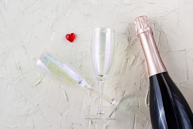 Valentines card with champagne glasses and bottle, heart and gift on white background. top view, copy space