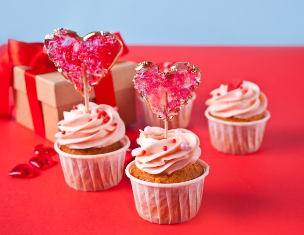 Valentines cupcake cream cheese frosting decorated with heart candy lollipop and gift box on the background.