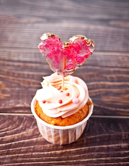 발렌타인 데이 컵 케 익 크림 치즈 설탕 장식 나무 배경에 심장 사탕 롤리팝으로 장식.