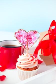ハートキャンディーロリポップで飾られたバレンタインカップケーキクリームチーズのフロスティング