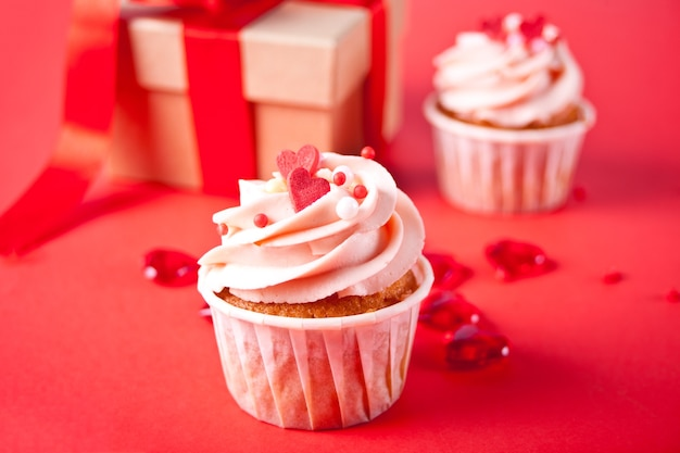 Valentines cupcake cream cheese frosting decorated with heart candy, mug of coffee and gift box