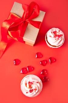 발렌타인 컵 케이크 크림 치즈 설탕 장식 빨간색 배경에 심장 사탕과 선물 상자. 발렌타인 데이 개념. 평면도.