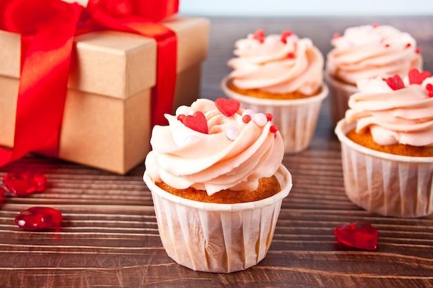 발렌타인 컵 케이크 크림 치즈 설탕 장식 나무 바탕에 하트 사탕과 선물 상자. 발렌타인 데이 개념.