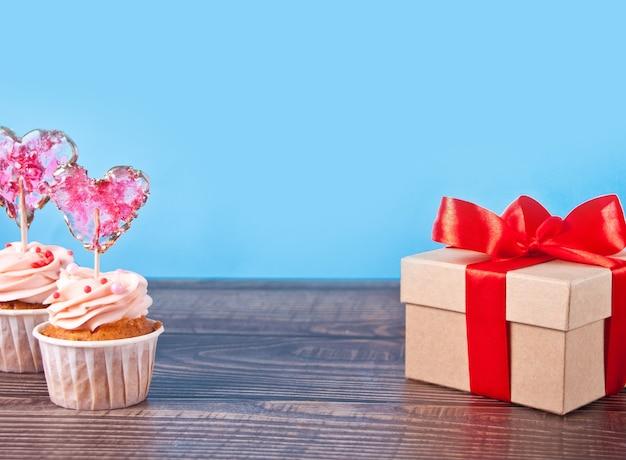 발렌타인 컵 케이크 크림 치즈 설탕 장식 하트 사탕 롤리팝 및 선물 상자. 공간을 복사하십시오.