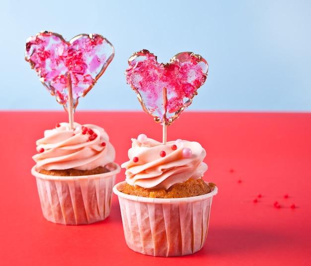 발렌타인 컵 케이크 크림 치즈 설탕 장식 빨간색 배경에 심장 사탕 롤리팝.