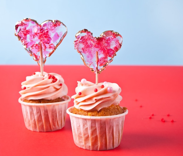 Valentines cupcakes cream cheese frosting decorated with heart candy lollipop on the red background.