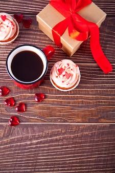 발렌타인 컵 케이크 크림 치즈 설탕 장식 하트 사탕, 커피 머그잔과 선물 상자. 발렌타인 데이 개념. 공간을 복사하십시오. 평면도.