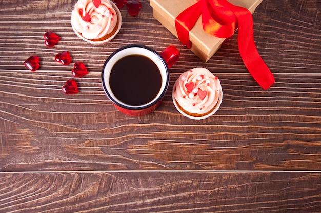 발렌타인 컵 케이크 크림 치즈 설탕 장식 하트 사탕, 커피 머그잔과 선물 상자. 발렌타인 데이 개념. 공간을 복사하십시오. 평면도. 프리미엄 사진