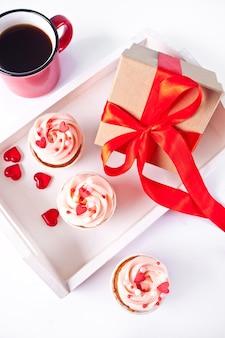 발렌타인 컵 케이크 크림 치즈 설탕 장식 하트 사탕, 커피 머그잔과 선물 상자. 발렌타인 데이 개념.