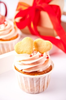 Valentines cupcakes cream cheese frosting decorated with heart shaped cookies and gift box on the background.