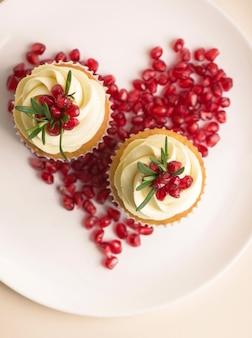 バニラのアイシングと赤いハートのバレンタインカップケーキ。