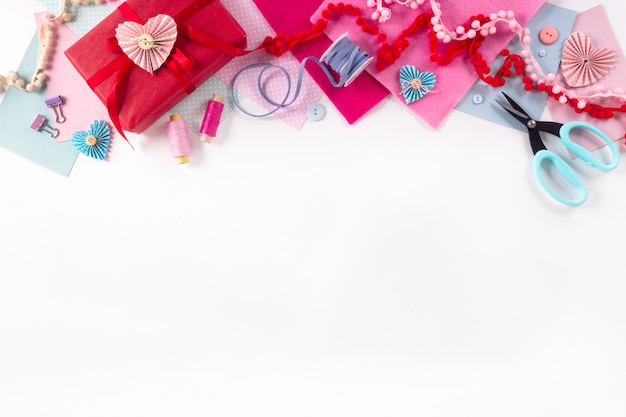 Valentines day and 14 february holidays banner. gift wrapping workspace. decoration presents making flat lay top view celebration preparation diy concept decor on white background. Premium Photo