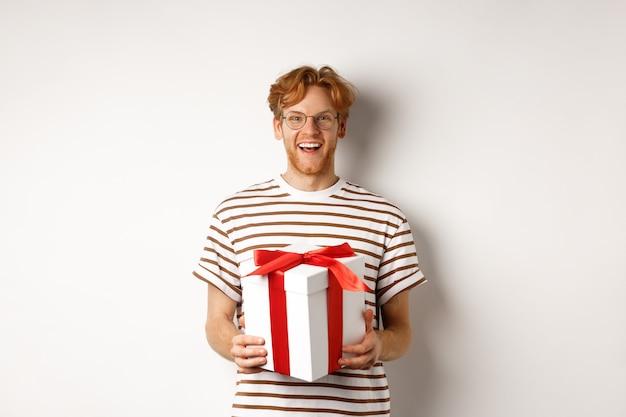 バレンタインデーと休日のコンセプト。ギフトボックスを保持し、感謝の笑みを浮かべて、プレゼントを受け取り、白い背景の上に立っている陽気な若い男。