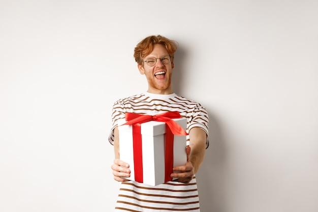 バレンタインデーと休日のコンセプト。幸せな赤毛の男は笑顔であなたにギフトボックスを与え、誕生日を祝って、白い背景の上に立っています。