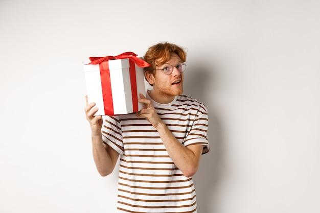 バレンタインデーと休日のコンセプト。彼の現在の箱の中の何を推測しようとしている興味をそそられた若い男。耳の近く、白い背景のギフトを振る赤毛の男。