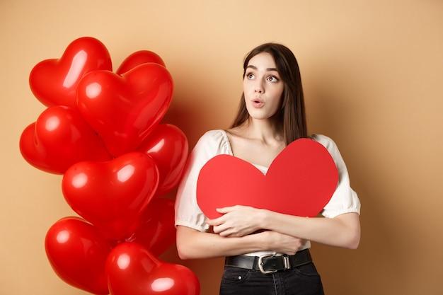День святого валентина и концепция любви заинтриговали нежную девушку, обнимающую большое красное сердечко и стоящую рядом с ...