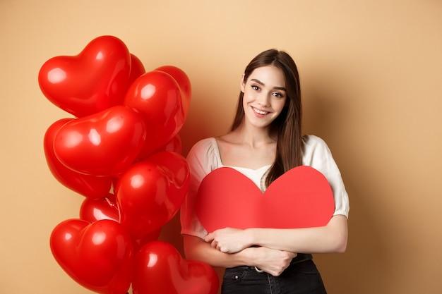 День святого валентина и концепция любви, милая девушка обнимает большое романтическое сердечко и улыбается, стоя ...