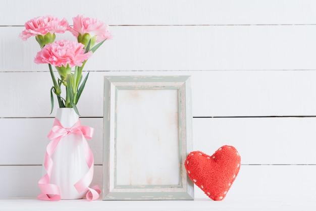 발렌타인 데이와 사랑 개념. 나무 배경에 꽃병에 핑크 카네이션입니다.