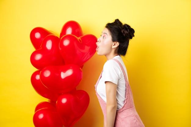 발렌타인 데이 및 관계 개념. 놀람의 젊은 아시아 여자 비명의 프로필, 와우 말하고 놀란 찾고 왼쪽 빨간 풍선, 노란색 배경 근처에 서 있습니다.