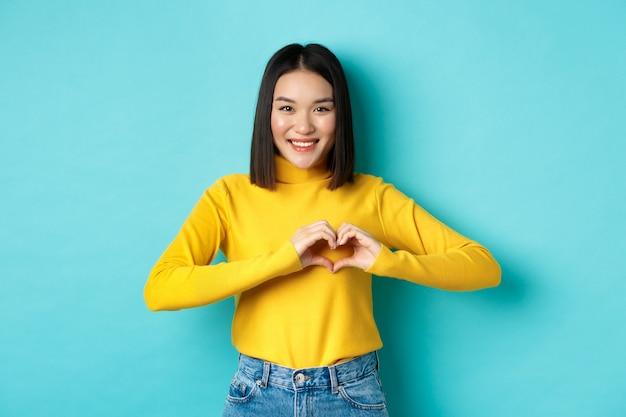 バレンタインデーとロマンスのコンセプト。美しいアジアの女性のショー私はあなたを愛し、ハートのジェスチャーと笑顔、青い背景に立っています。