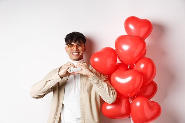 День святого валентина и концепция романтики. красивый молодой человек, стоящий возле красных сердец воздушных шаров и показывающий жест сердца, влюбленный и улыбающийся, белый фон.