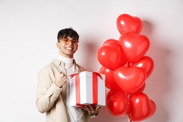 バレンタインデーとロマンスのコンセプト。幸せで自信を持って彼氏は恋人への贈り物を準備し、はいと言って笑って、ロマンチックな贈り物を持って、赤いハートの風船の近くに立っています
