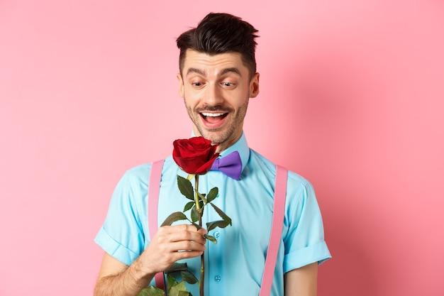 バレンタインデーとロマンスのコンセプト。ピンクのロマンチックな背景の上に立って、蝶ネクタイで恋人を待っている間、赤いバラを見て幸せな彼氏。