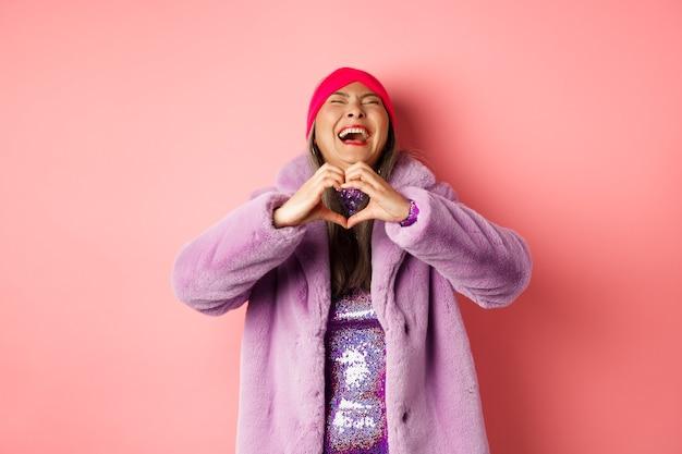 バレンタインデーとショッピングのコンセプト。ピンクの背景にフェイクファーで立って、ハートのサインを示し、のんびりと笑うスタイリッシュな衣装で幸せなアジアの女性。