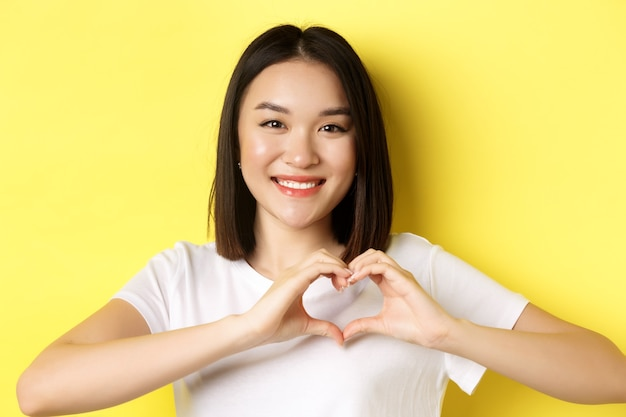 バレンタインデーと女性のコンセプト。白いtシャツを着たかわいいアジアの女の子のクローズアップ、笑顔と心を示して、私はあなたのジェスチャーを愛し、黄色の背景の上に立っています。