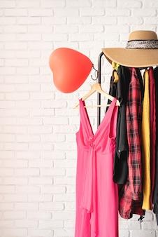 발렌타인 데이 및 여성의 날 개념. 데이트를위한 다양한 여성 의류와 핑크 드레스의 의류 랙 가을