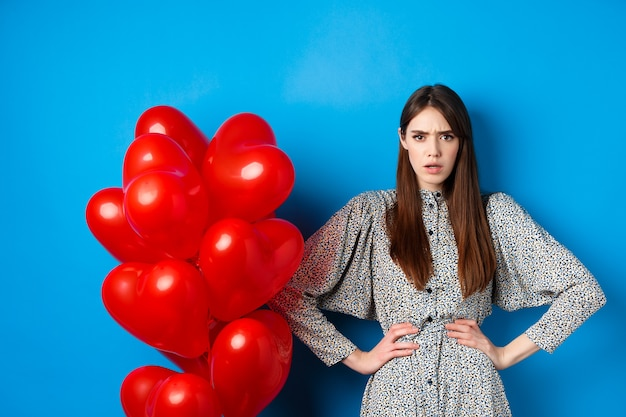 Valentines day. angry and confused girlfriend in dress, standing near red heart balloons and frowning annoyed at camera, standing near blue background.