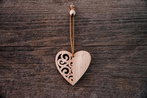 1つの木製の装飾的なハートトップとグランジスタイルのバレンタインデーの背景茶色の自然なボード...
