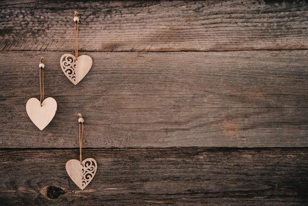 3つの木製の装飾的な心とグランジスタイルのバレンタインデーの背景茶色の自然なボード...