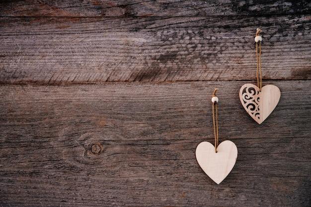 2つの木製の装飾的なハートトップとグランジスタイルのバレンタインデーの背景茶色の自然なボード...
