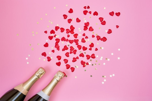 Valentines day background. champagne bottles, red hearts and golden confetti on pink background.