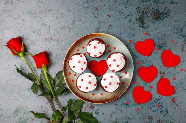 Valentines day background, chocolate cupcakes with heart shaped candies,top view